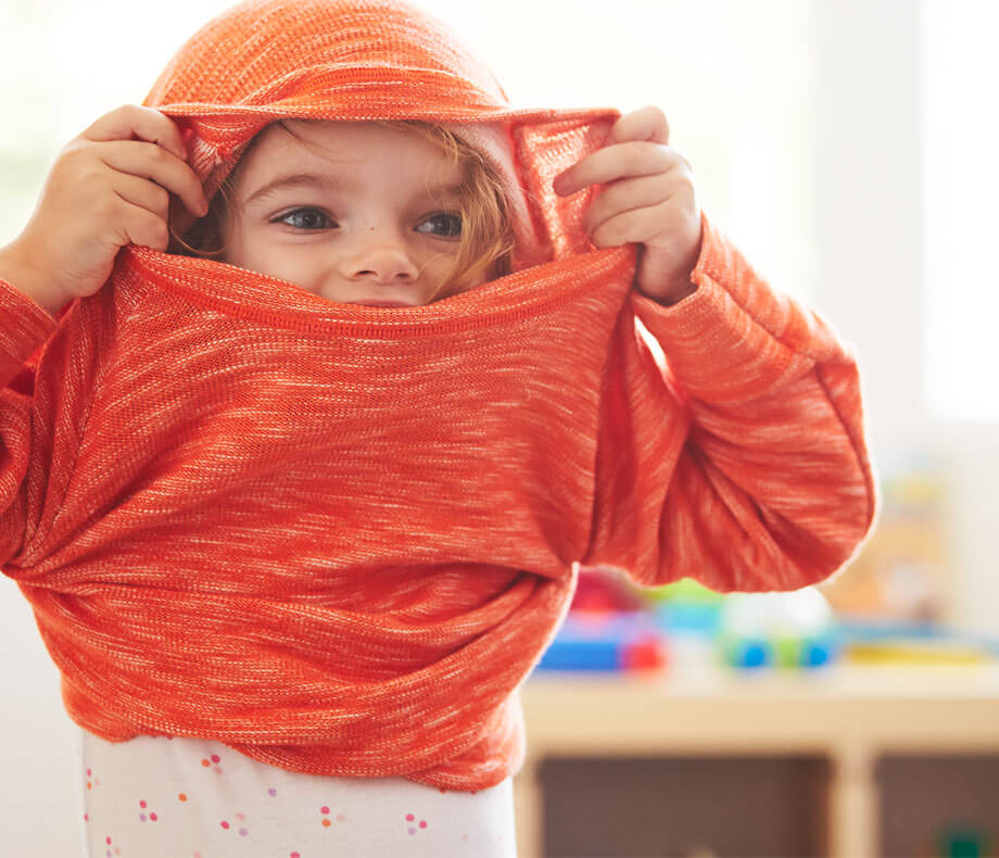 Young girl pulling a sweater over her head and smiling.